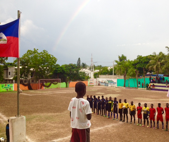 As the players walked out onto the field, the Haitian National Anthem played, the red and blue flag of Haiti waved in the late day breeze, and a perfectly timed rainbow arched over the Park.  This moment captures so much of what is special about  Park Izmery, the kids, and the game.
