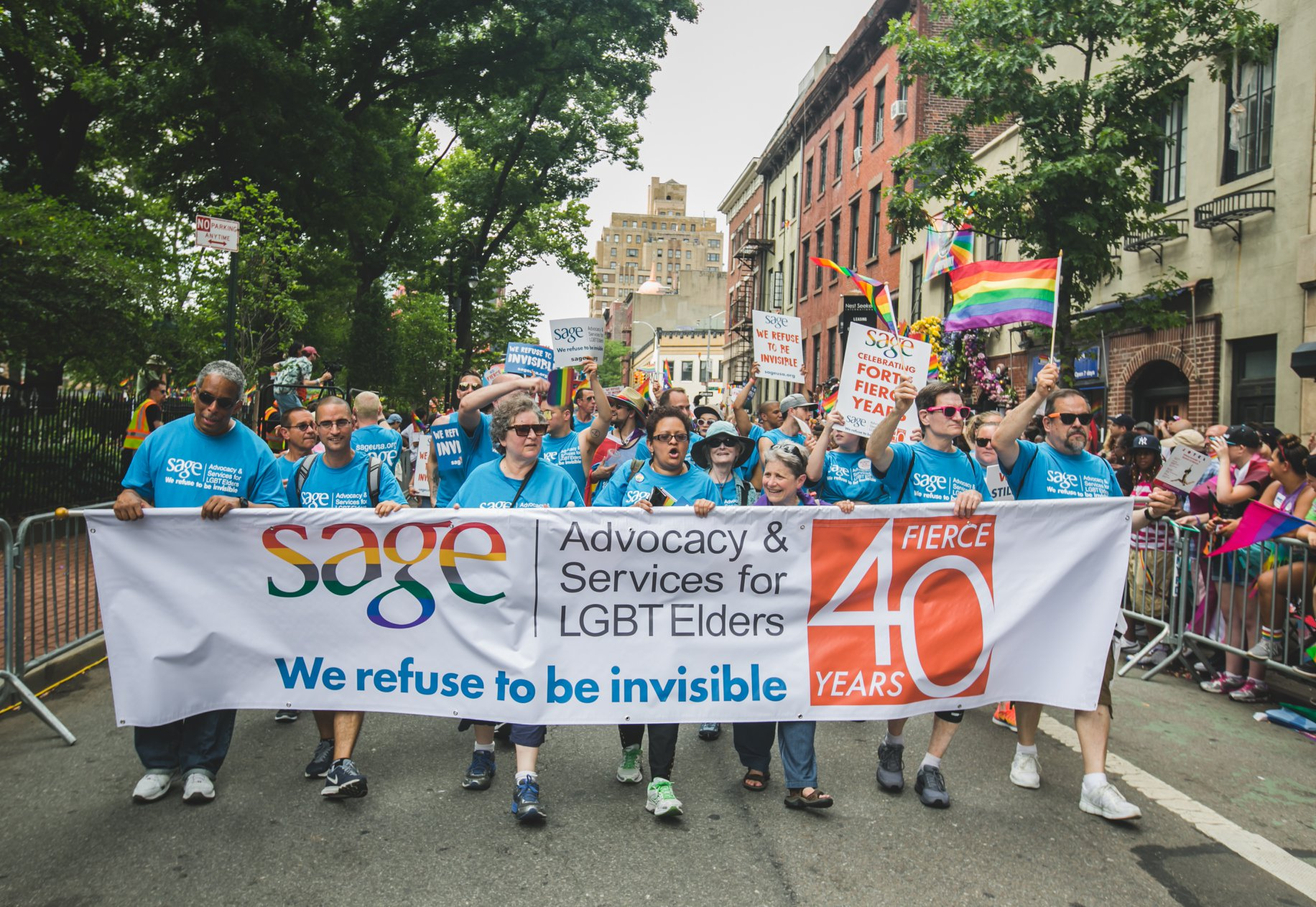 Sage with a banner at a Pride parade.