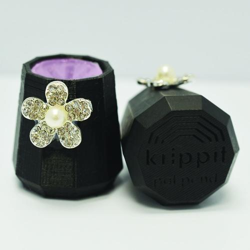 A black and pink Krippit with a jeweled flower.