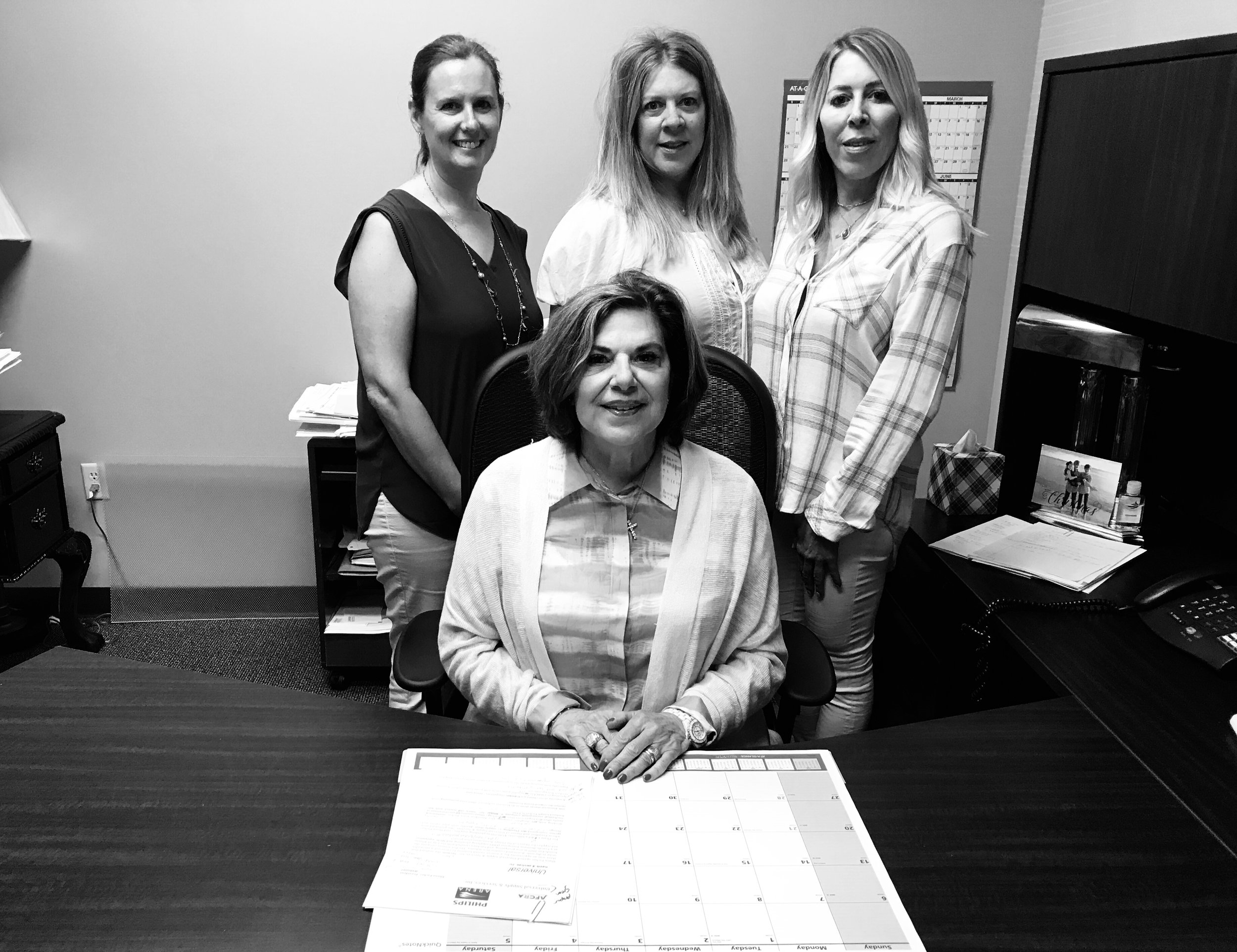 Universal Services and Supply, Inc., President Diana Escher (seated) with her staff .