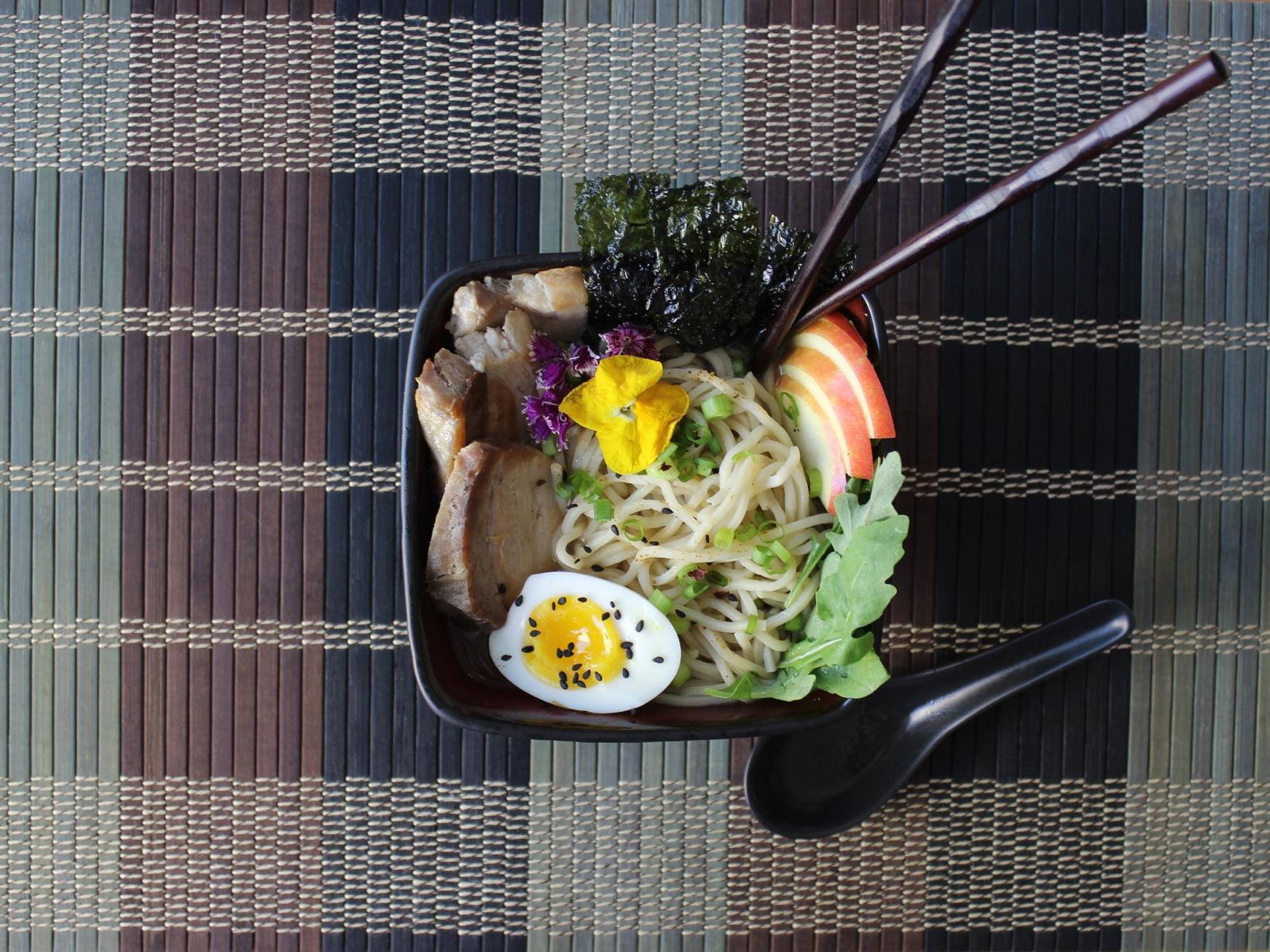 Miso Veggie Ramen Kit    prepared with soft-boiled egg, black sesame seeds, pan-fried pork, nori, apples, arugula, green onions, and edible flowers to garnish.