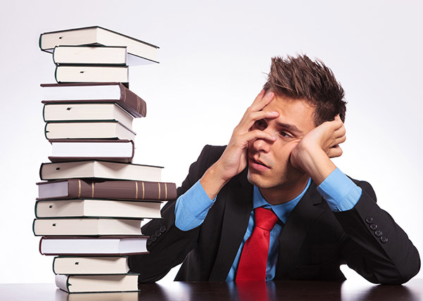 businessman frustrated with pile of books.jpg