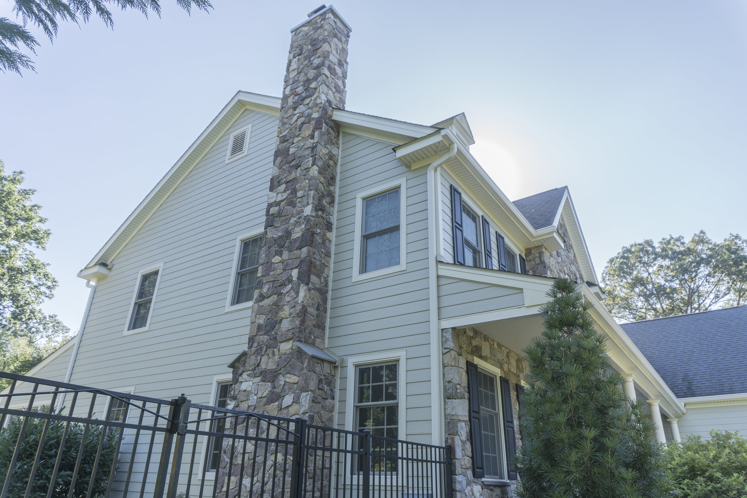 Hardie siding complementing a newly renovated stone chimney.