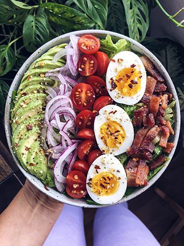 Whole30 Cobb salad made with avocado, thinly sliced onions, cherry tomatoes, soft boiled eggs, organic bacon and romaine lettuce.
