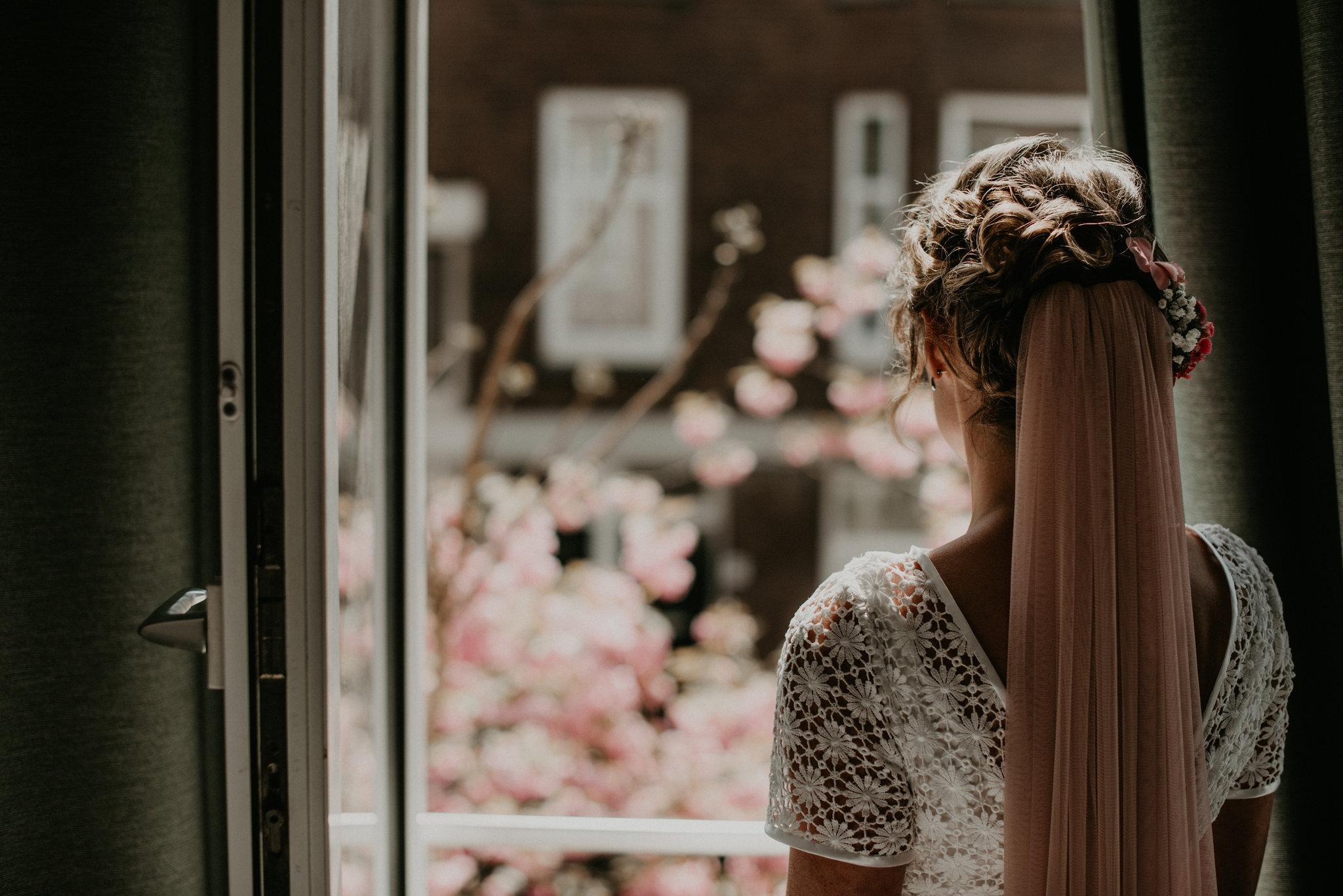 Rotterdam bride looking our her bedroom window looking for her groom