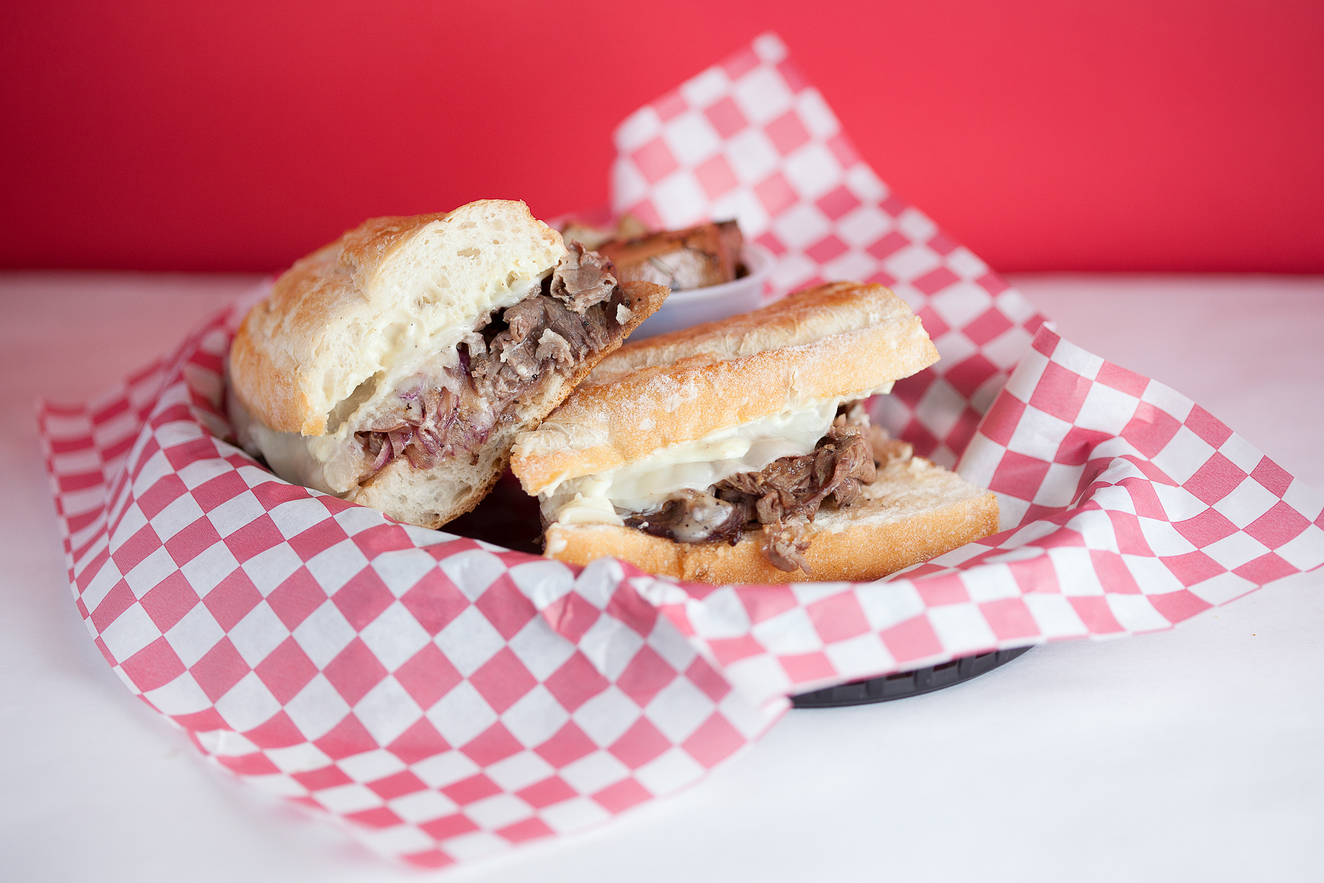 Prime Rib Philly - Alderwood slow smoked prime rib tossed with hardwood smoked provolone, grilled onions, jus, and smoked garlic mayo on a Pearl Bakery French baguette. Comes with one free side. (Gluten-Free bread available)11.25/14.50