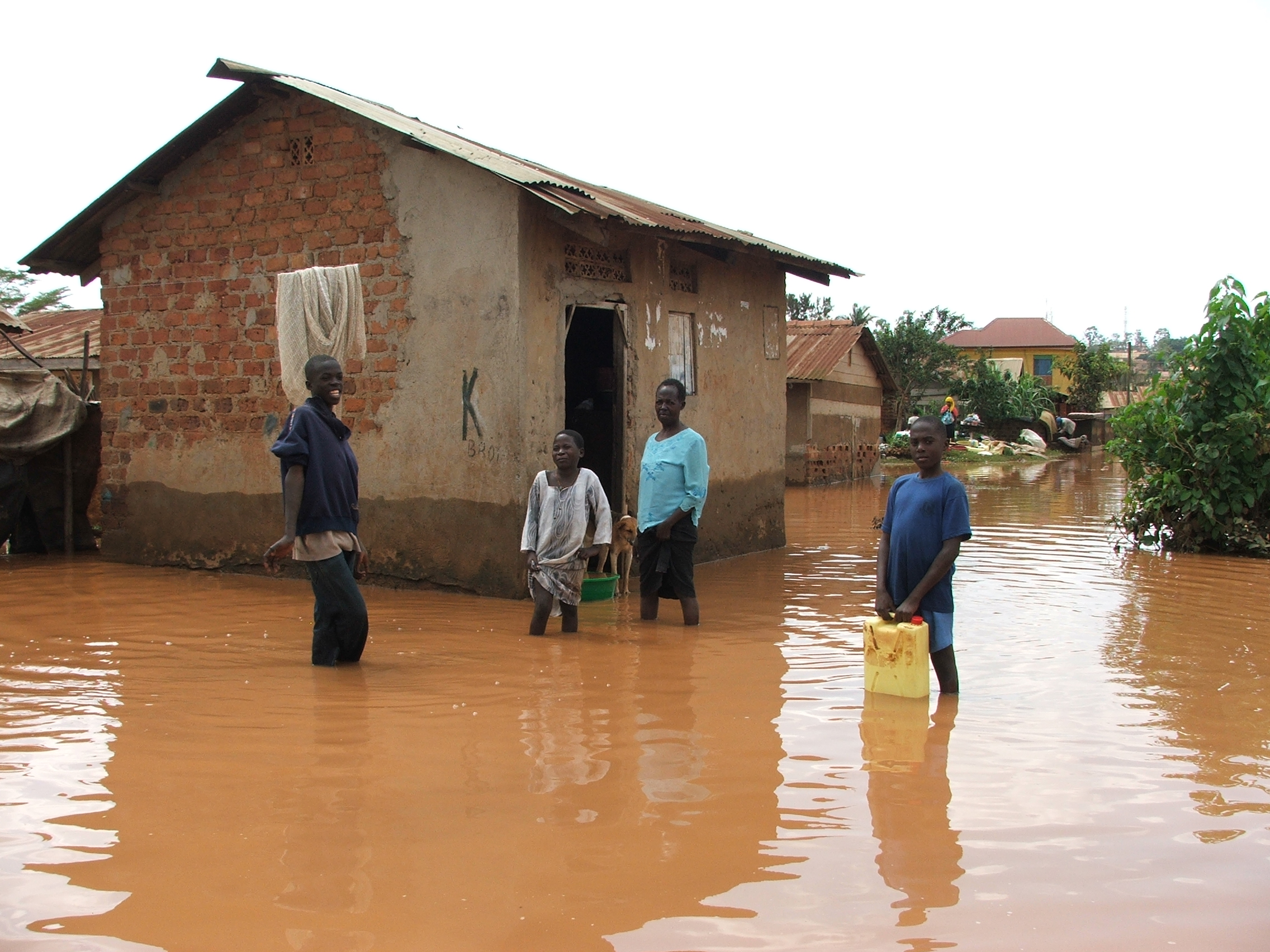 Regina & Jaliya outside their their home during one of the many floods they experience in Bwaise