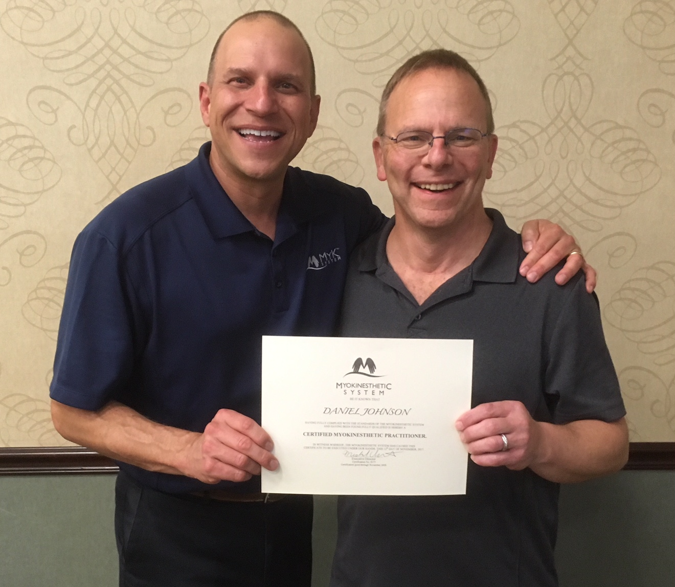 Dr. Michael Uriarte, founder of MYK, giving Dan his re-certification for MYK