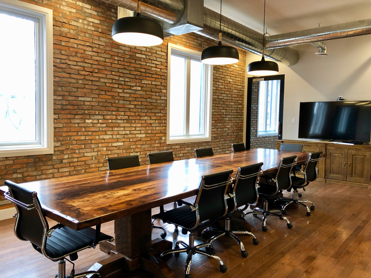 Brick-And-Beam Office - Malleum transformed this yellow cinderblock-walled room at The Wellington into a contemporary, brick-and-beam office. Additional windows, and new, glass-walled interior rooms, bathe the entire space in sunlight.Building upon Hamilton's storied history, the accent walls feature reclaimed local brick, the conference table is made from reclaimed barn board, and the light fixtures have an industrial aesthetic.
