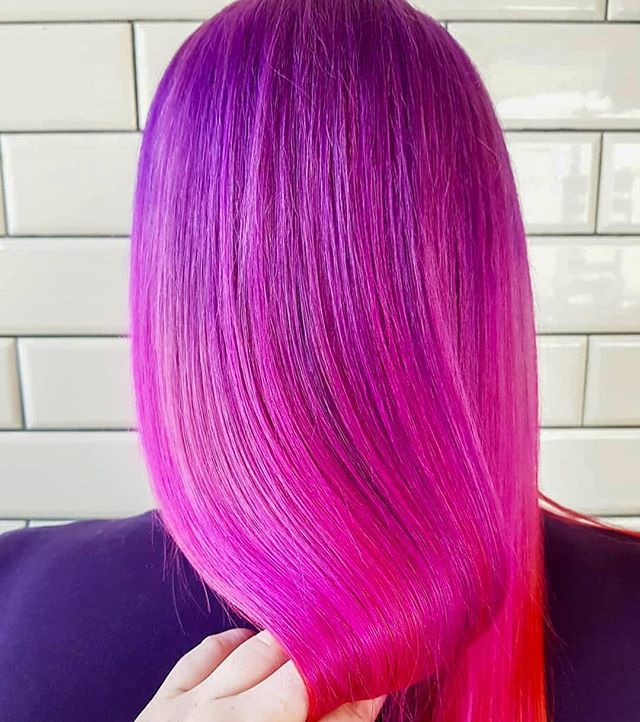 Stunning sunset bleed by Tia 😍 Want a dusk-inspired look like this? Send us a message to book your appointment today 💕✨ • • • #pinkhair #purplehair #goldwell #haircolor #colormania #modernsalon #vividhaircolour #haircolor #iamgoldwell #licensedtocreate #hairart #colorfulhair #orangehair