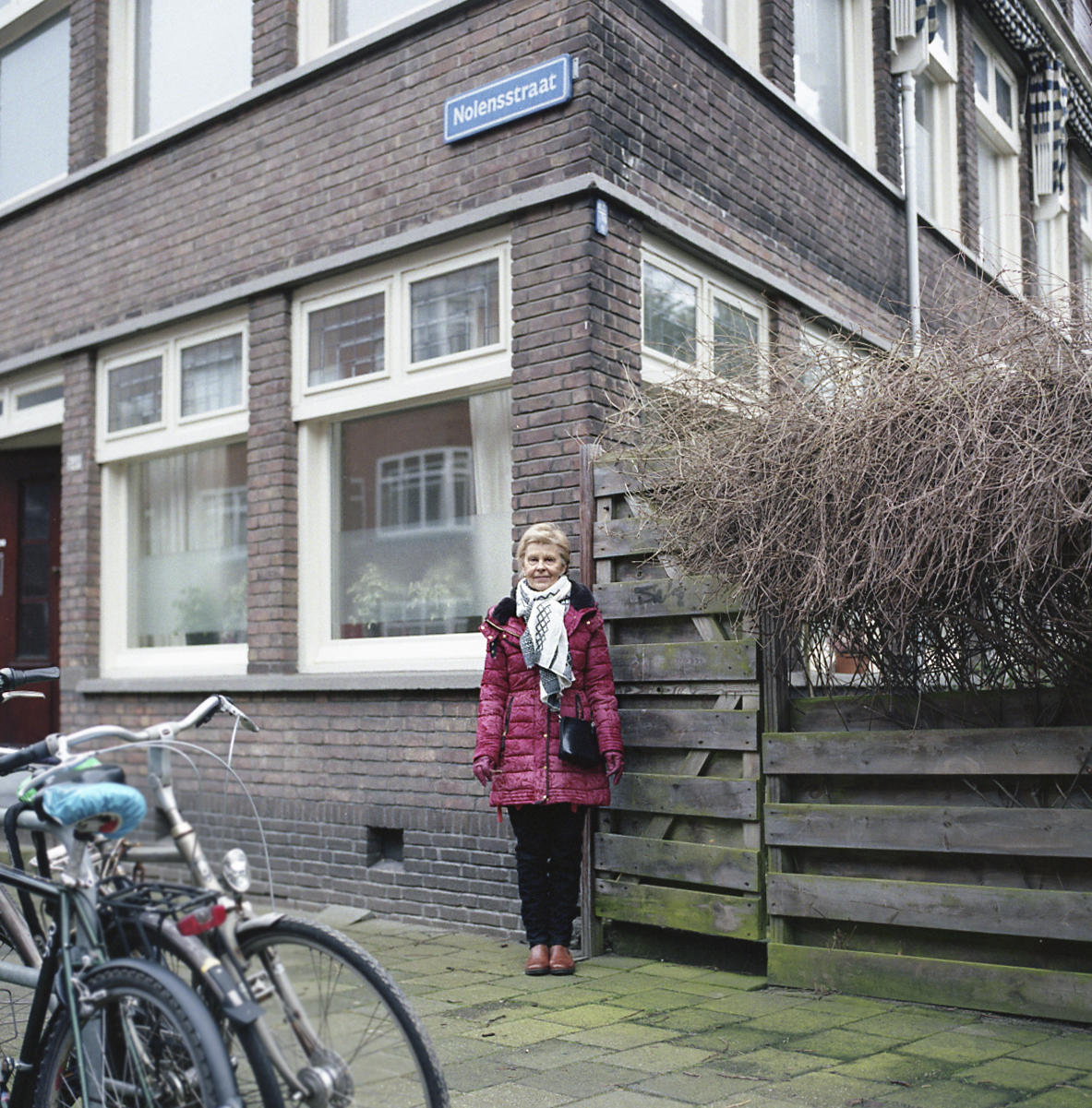 """Mom - """"I used to live in the Nolensstraat.""""   My mom mentioned 'Nolensstraat' several times. Almost everytime she visited me in Rotterdam. I remembering her telling the story of living in this street and me finding it. I used to bike through this street almost everyday for 2 years. Seeing the street sign and thinking to myself """"I should tell her I found the street, so we can go there"""" but it would slip my mind a few minutes later. So I never actually told her until we took a walk around the block. I finally remembered! It was perfect because I had my camera with me so I could take a picture of her and the street sign. Now all I have to do is show her the picture."""