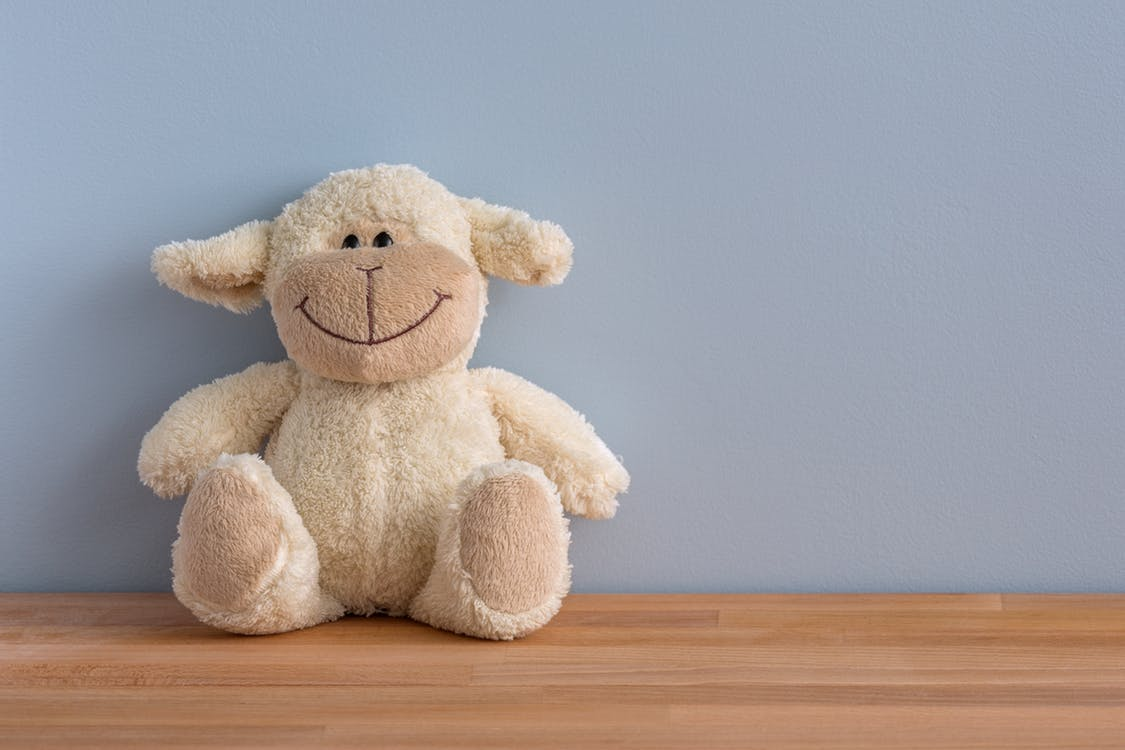 Whites sheep stuffed animal sitting up against grey wall