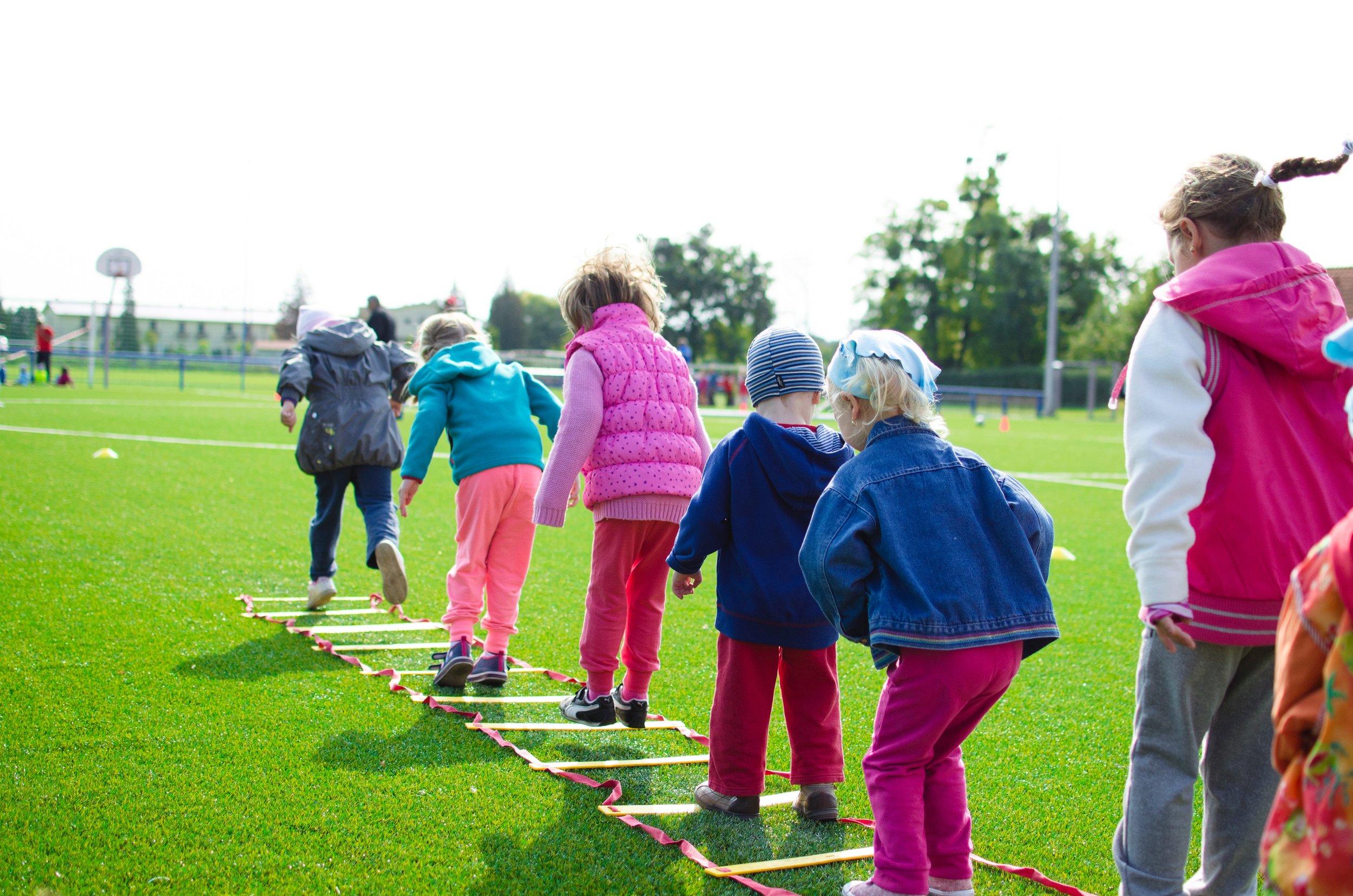 Five children jumping through rope ladder on an grass field