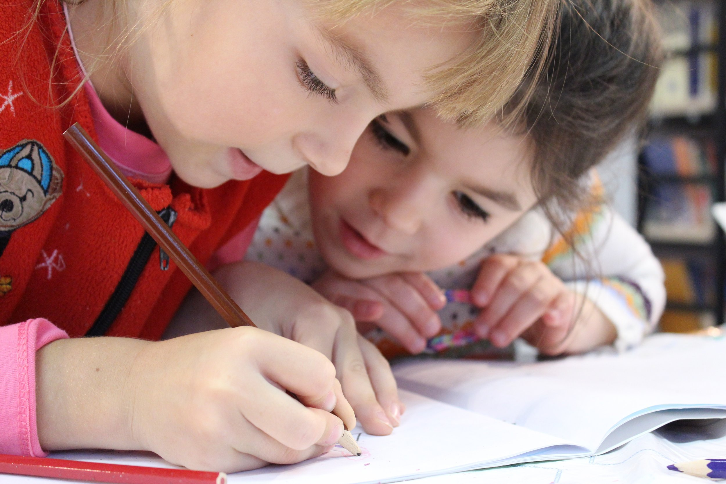 Two girls hovering over a notebook and writing together