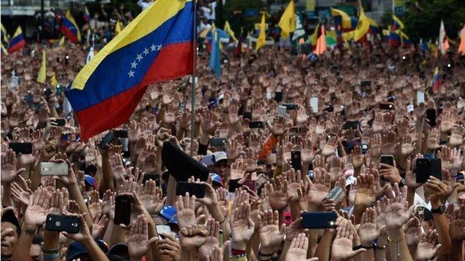 ¿QUÉ ESTÁ PASANDO EN VENEZUELA?    Los ciudadanos de Venezuela están enfadados. Hay una crisis política y llega al punto de ebullición. El país sudamericano está atrapado en una espiral descendente debido al gran aumento de hiperinflación y crimen, cortes eléctricos y escaseces de alimentos y medicina…   Por Timi Obatusin