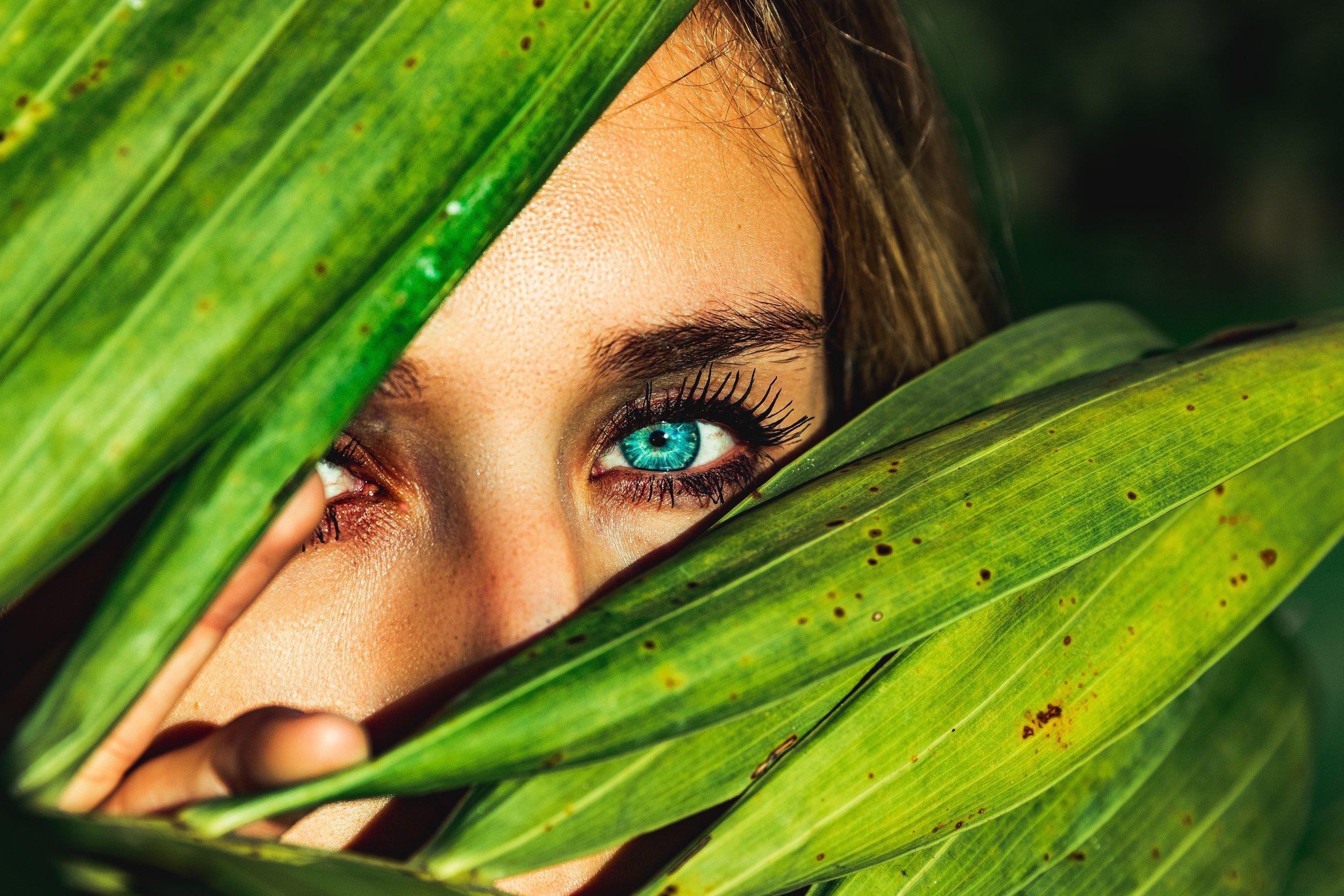 woman peering through leaves.jpg