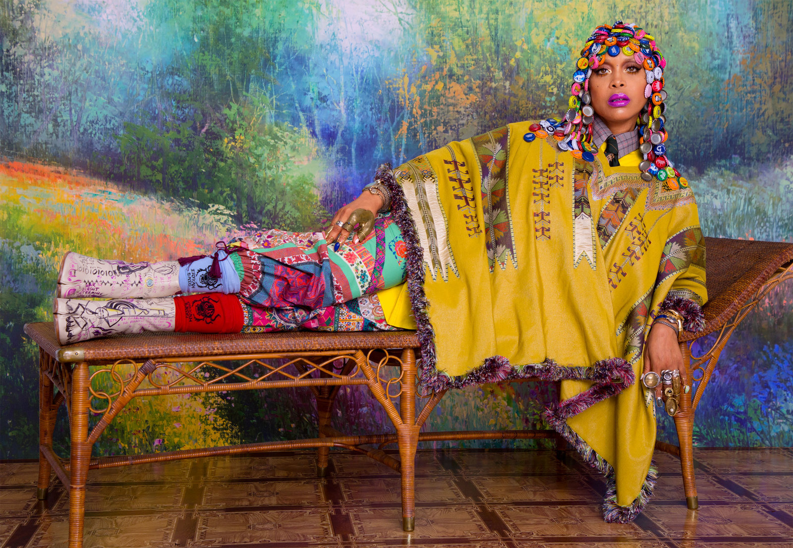 Badu in an Etro cape and pants and Raf Simons coat, shirt, and tie. From Badu's collection: a Badu x Chioma Obiegbu headpiece; a Badu x Lillian Shalom grill; Angostura rings and finger casts; Into Into nail rings; watches and bracelets; Badu World Market socks; and Maison Margiela tabi boots custom designed by Badu