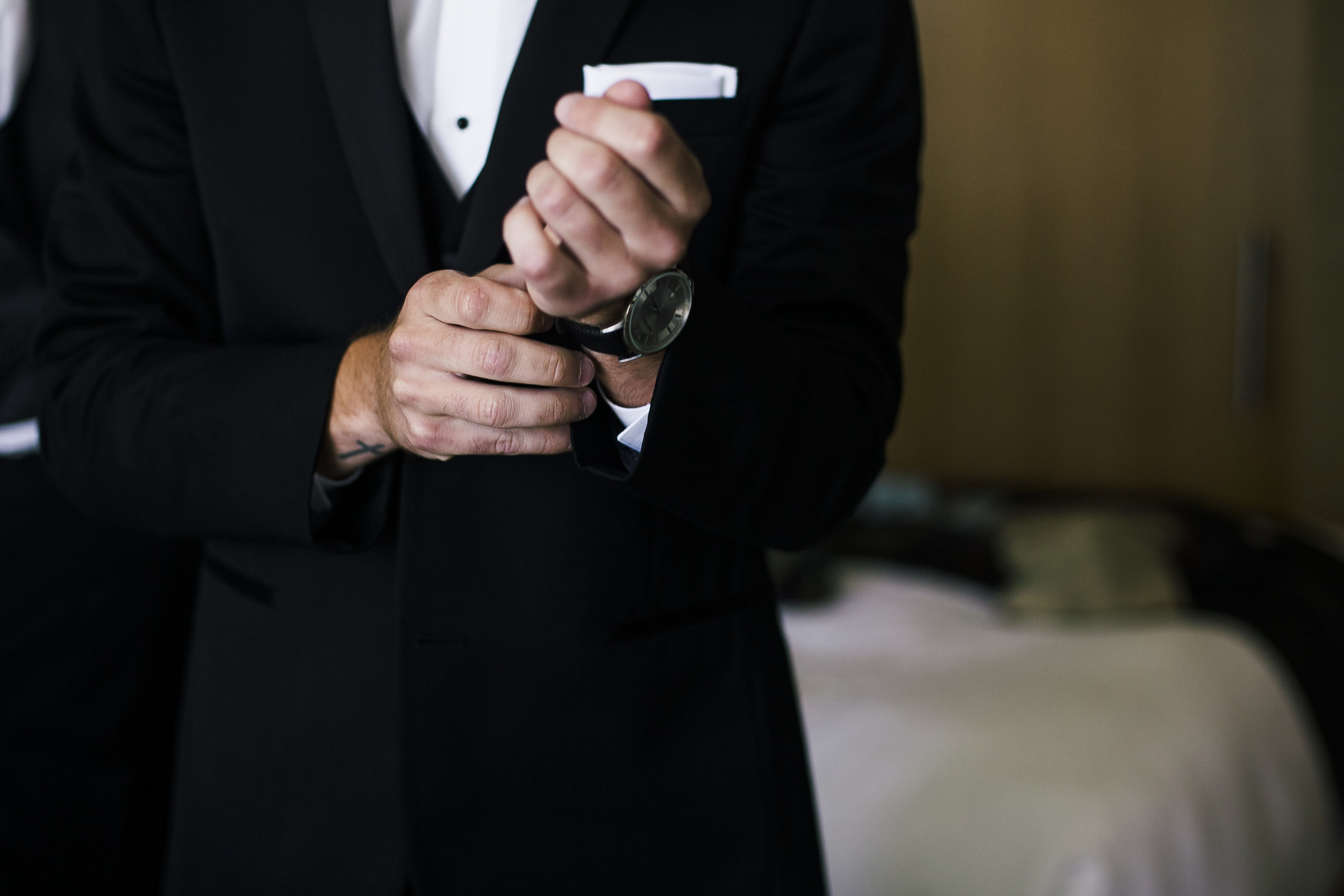 groom putting watch and cufflinks on