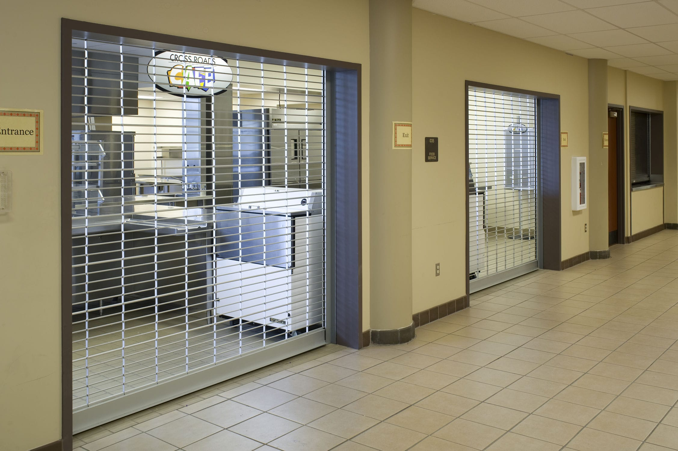 "Security Grilles - Security Grilles provide security against unwanted entry while still providing visibility and air flow. Manufactured with 5/16"" solid aluminum rods with various-sized chain constructed of eyeletted aluminum is spaced at customized intervals. They coil above openings typically in schools, malls, healthcare settings and more."
