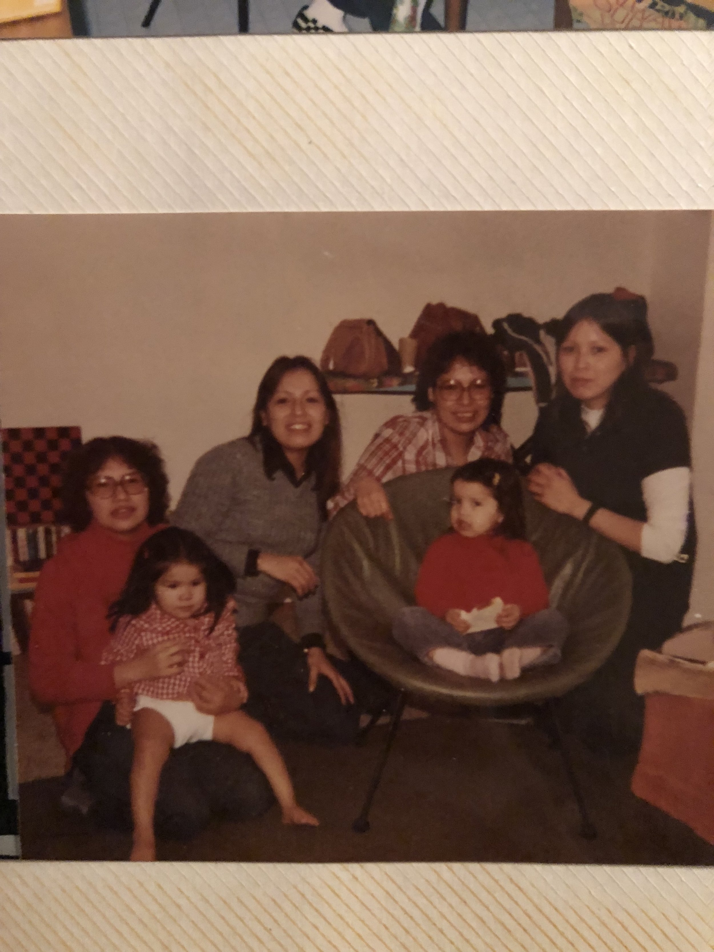 My mother on the far right with my two aunts to her right, their cousin, my second cousin and me in the green chair.
