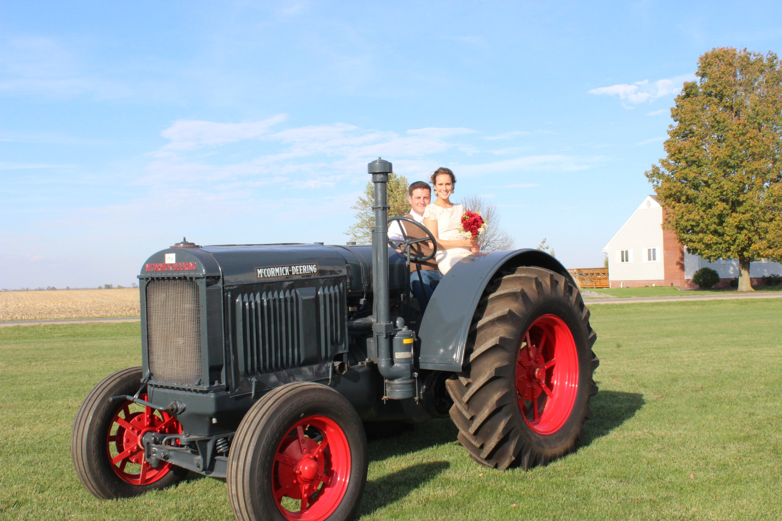 Brandt and Kelsey on their wedding day, posing with her great grandfather's very first tractor.