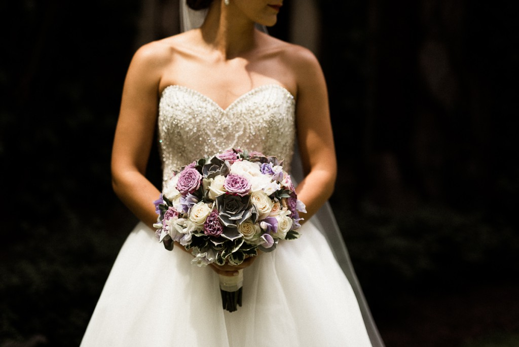 Bride holding purple and white bouquet with succulents