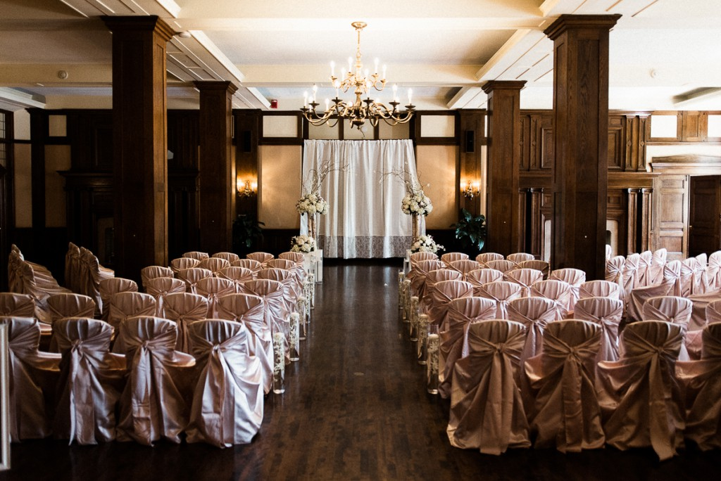 Wedding ceremony set-up at Minneapolis club with pink satin chair covers and orchid arrangements