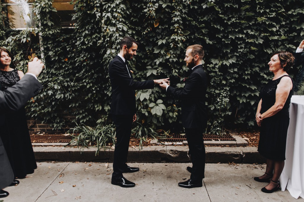 Exchanging of the rings, same-sex outdoor wedding ceremony in Linden Hills Minnesota