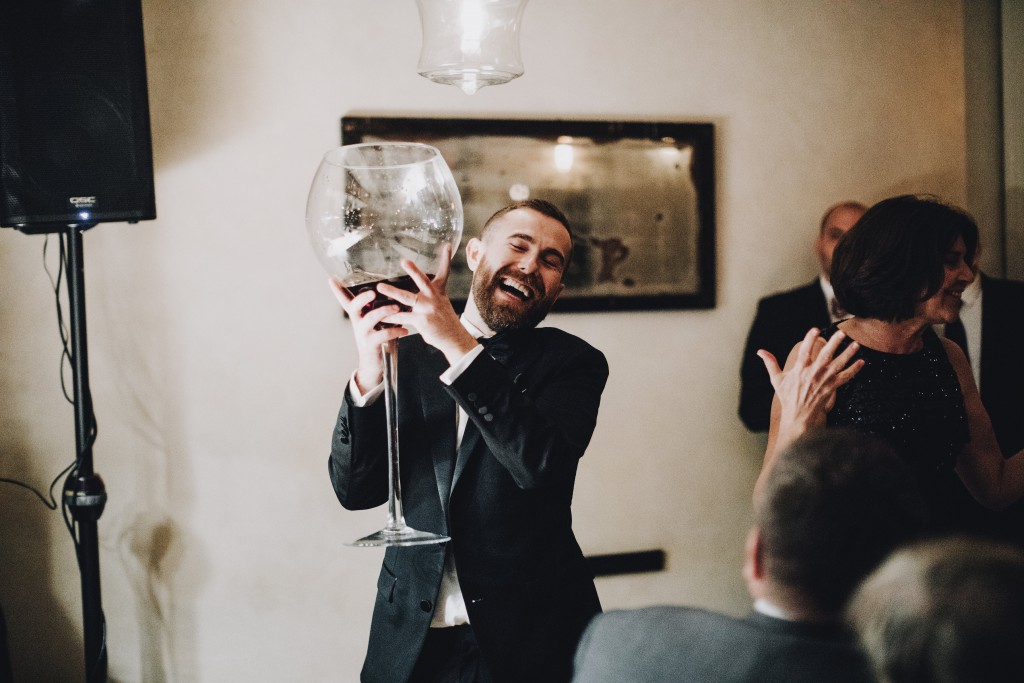 groom holds massive glass of wine during roast toasts for wedding reception at Tilia in Linden Hills, Minnesota