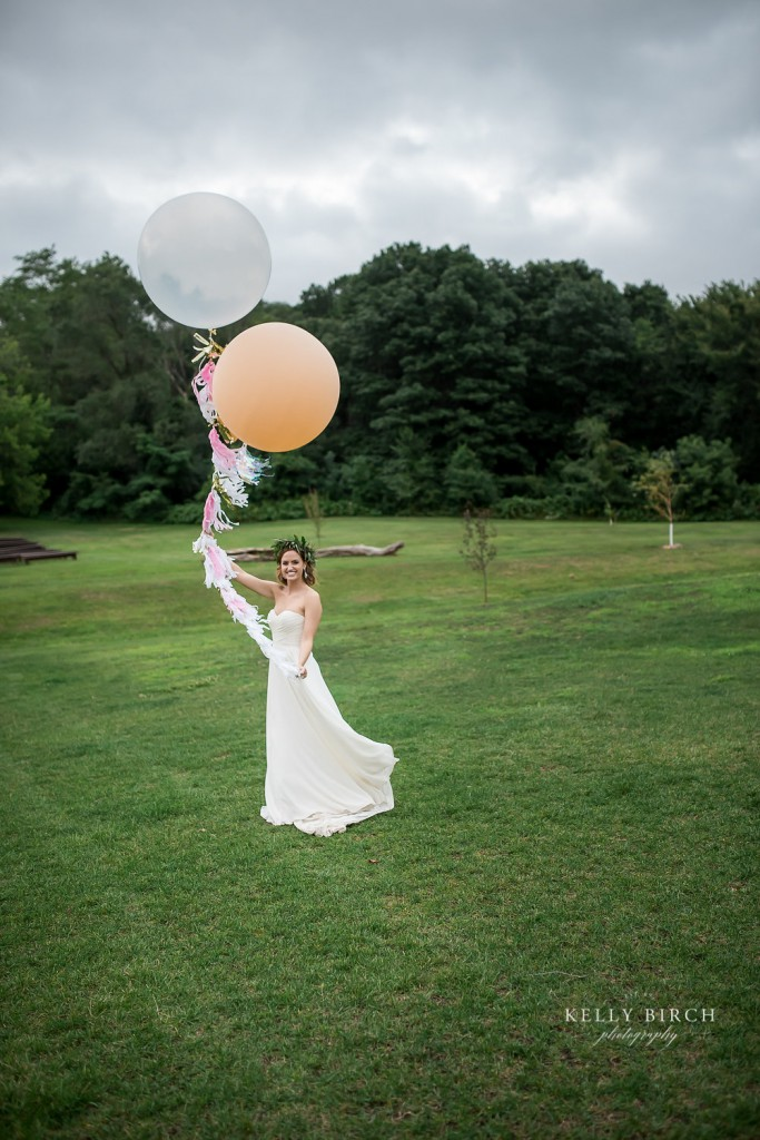 Bride holding large round balloons on the grounds of Historic Hope Glen Farm