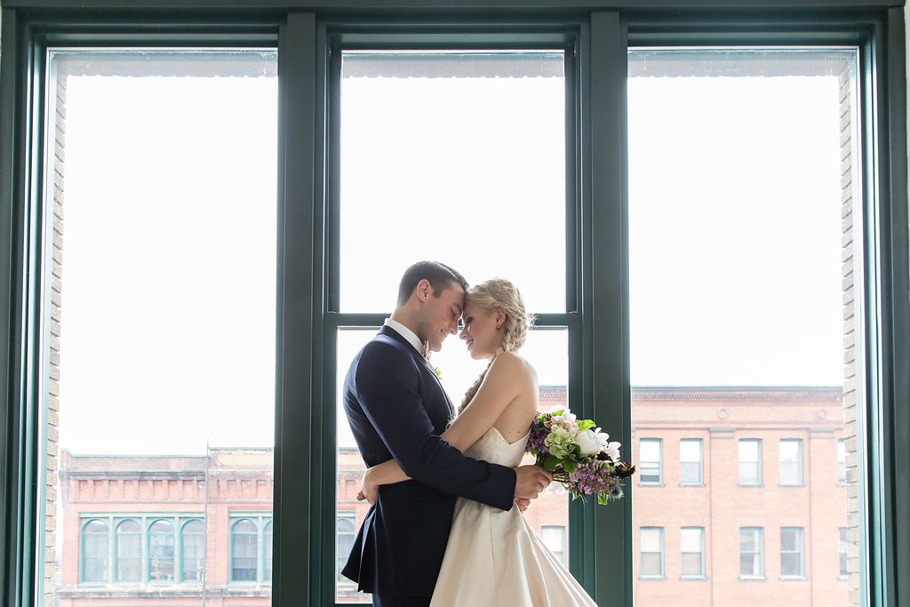 Bride and groom pose for portrait in front of large window
