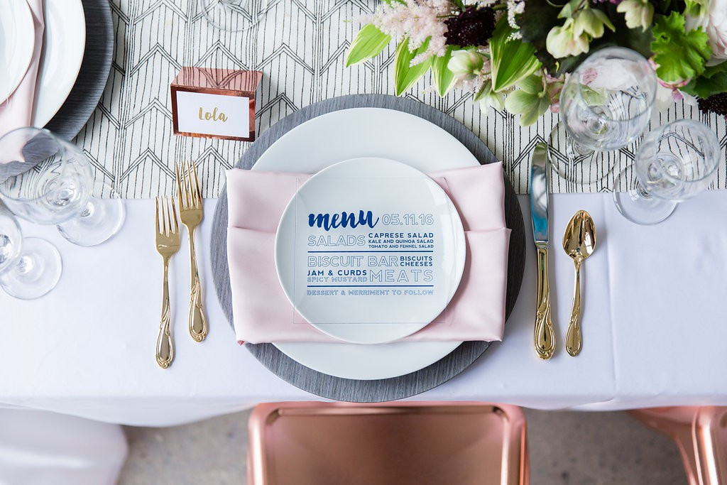 Modern table setting with pink napkin, gray wood charger, gold flatware and patterned table runner