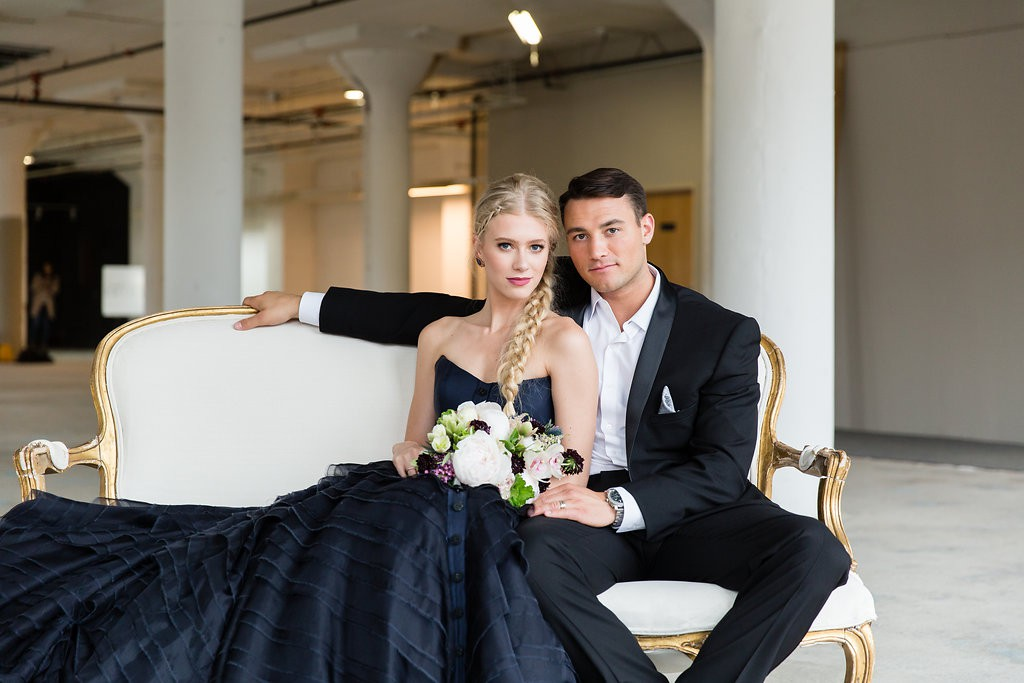 Bride's second dress in deep navy/black, posing with groom on vintage soft