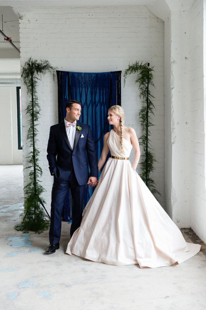 Bride and groom holding hands in front of ceremony backdrop