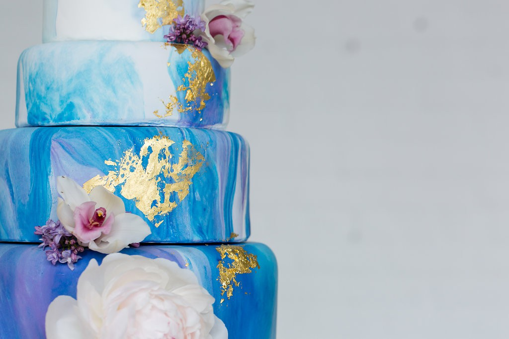 four tier watercolor and gold foil cake with real flower accents