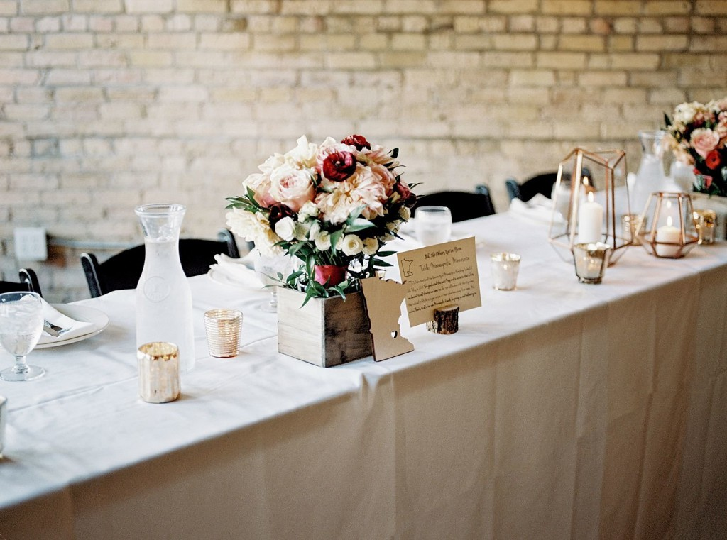 Fall florals in pink, peach and red shades with a rustic twist. Dahlias, roses, hydrangea, greenery. Paired with geometric lanters and table names/numbers by state