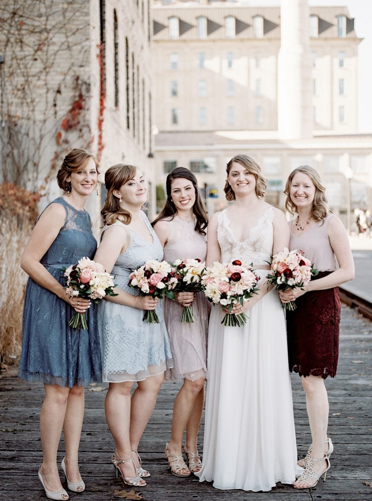 Mismatched bridesmaids in burgundy and blue tones with bride