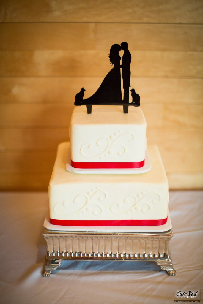 simple two tier wedding cake with red ribbon and custom cake topper