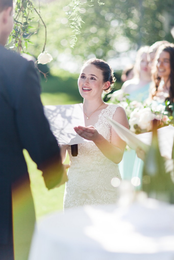 Bride reading vows during outdoor wedding ceremony at red barn farm
