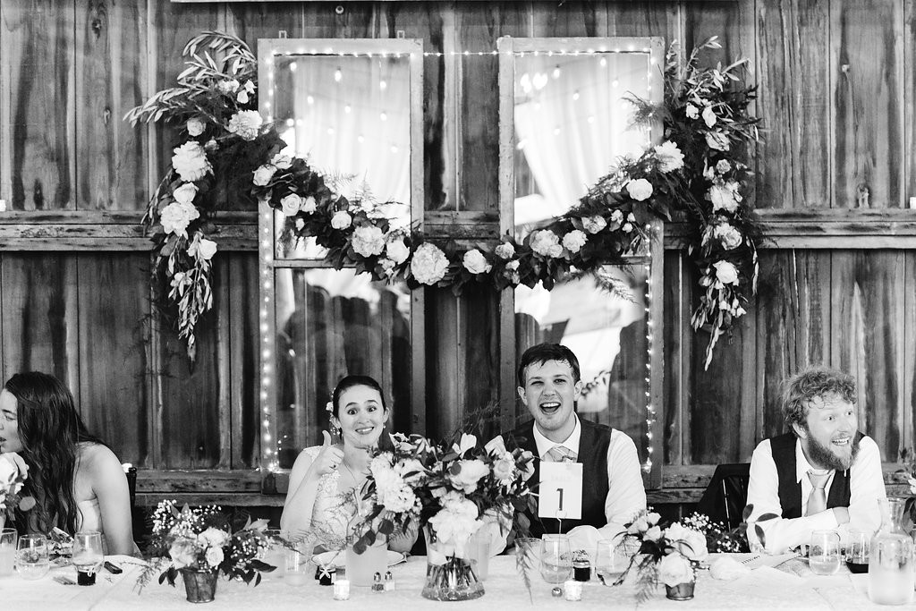 bride and groom sitting at head table during reception at Red Barn Farm