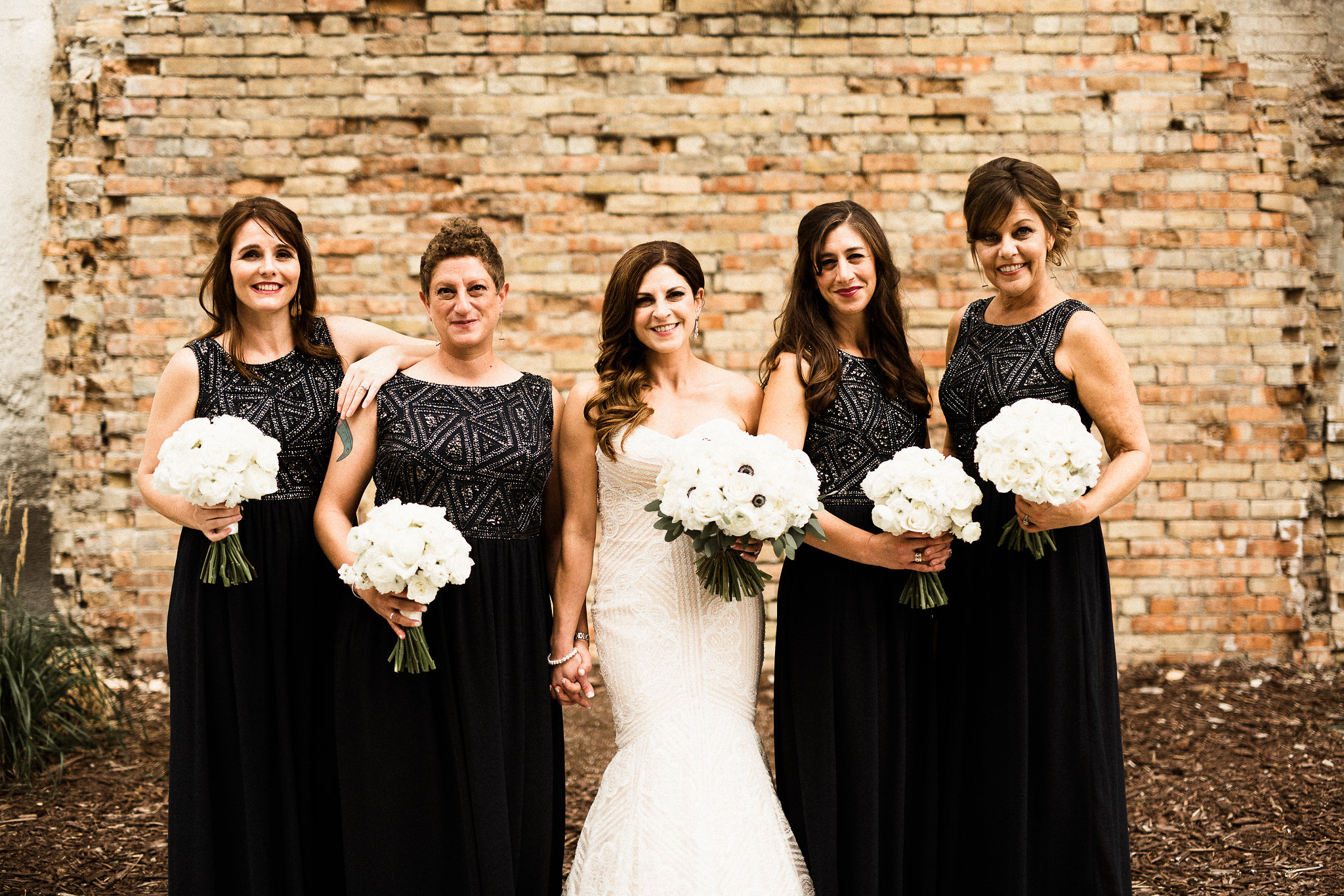 bride and her bridesmaids hold white bouquets