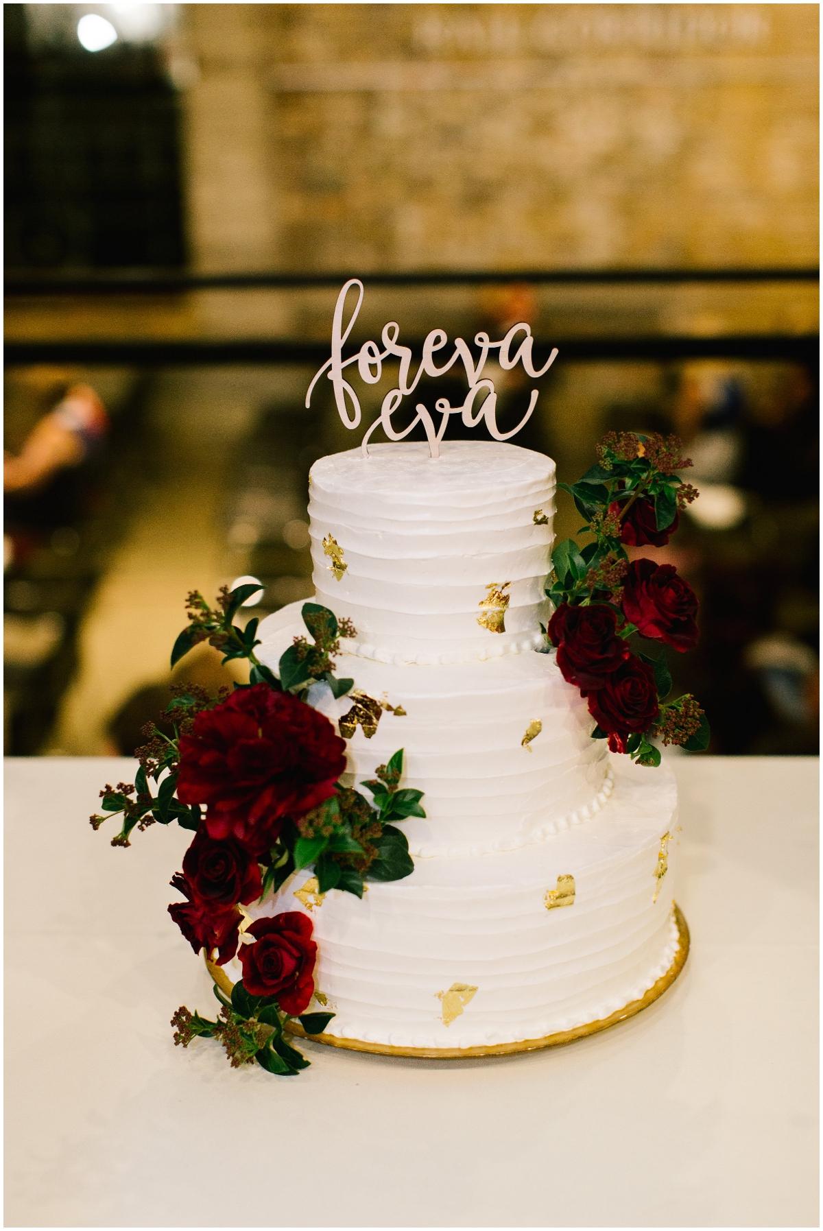 Burgundy, greenery, and gold wedding cake