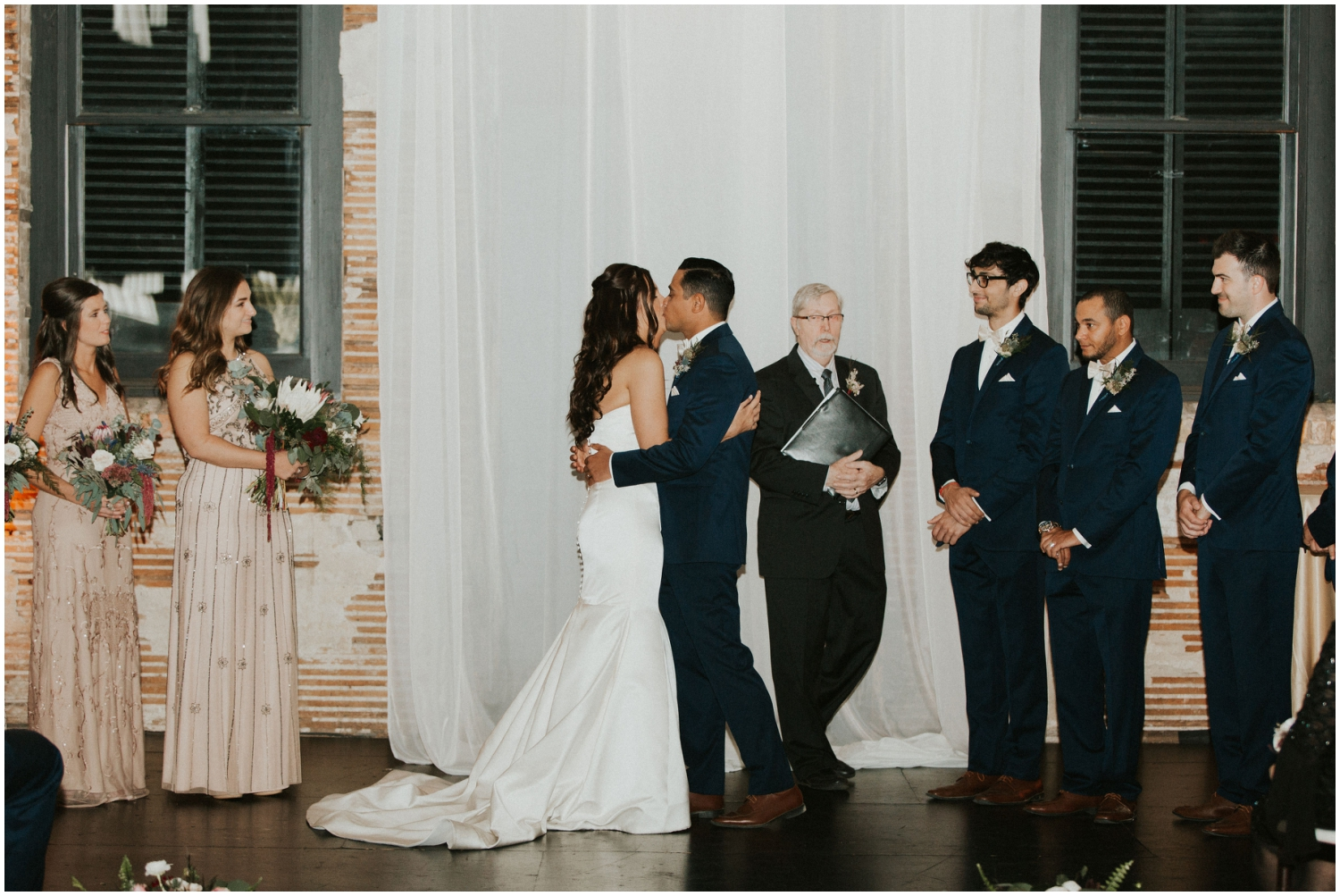 Bride and groom kiss at their wedding ceremony