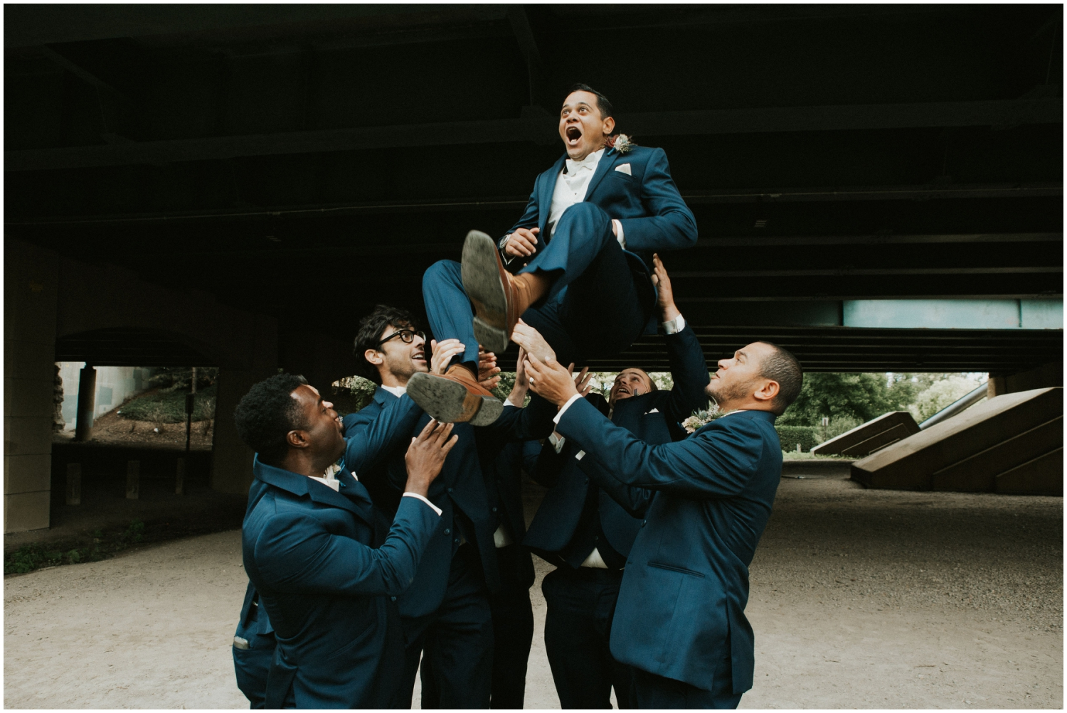 Groomsmen carrying the Groom up in the air