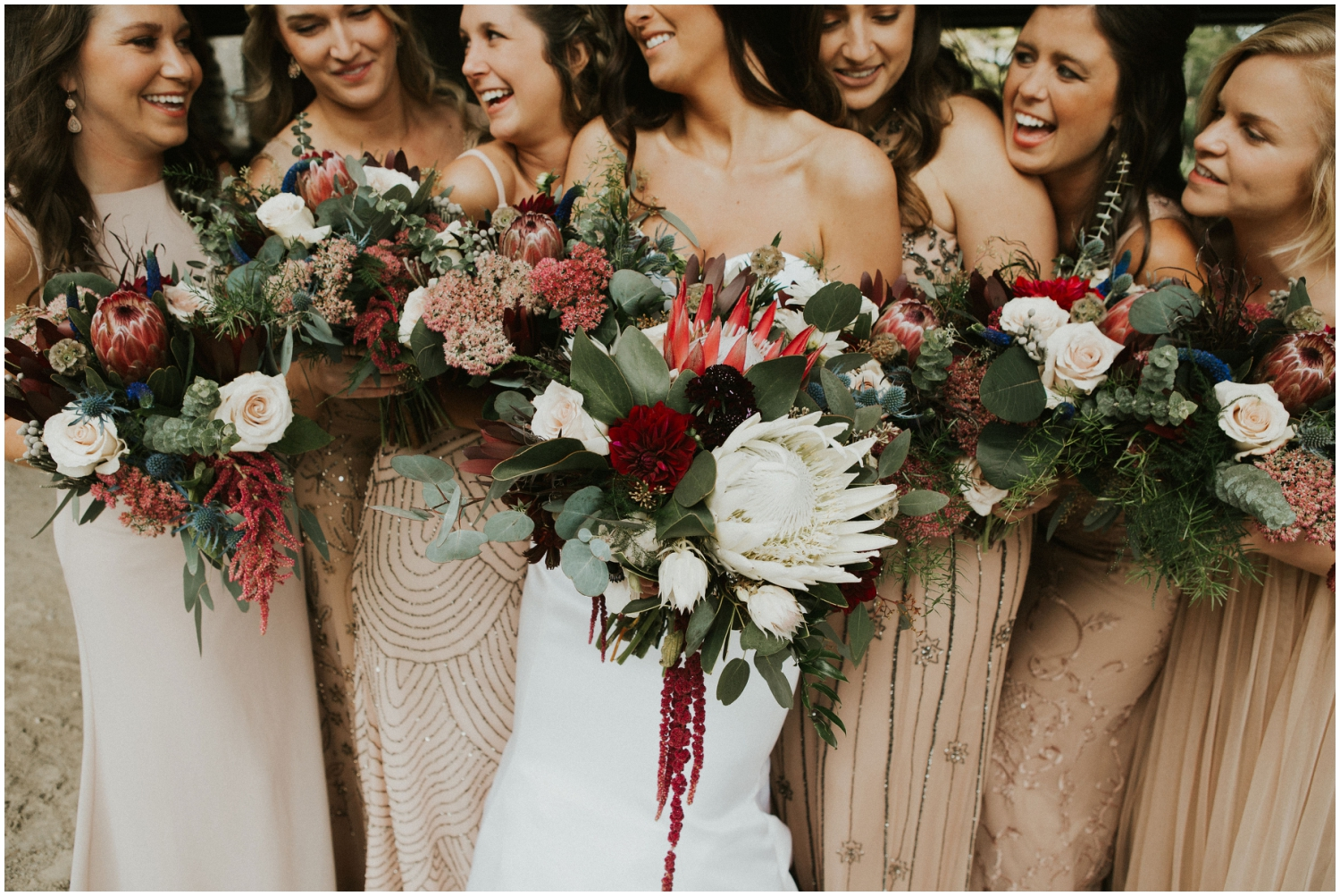 Bride and her bridesmaids holding gorgeous burgundy wedding bouquets