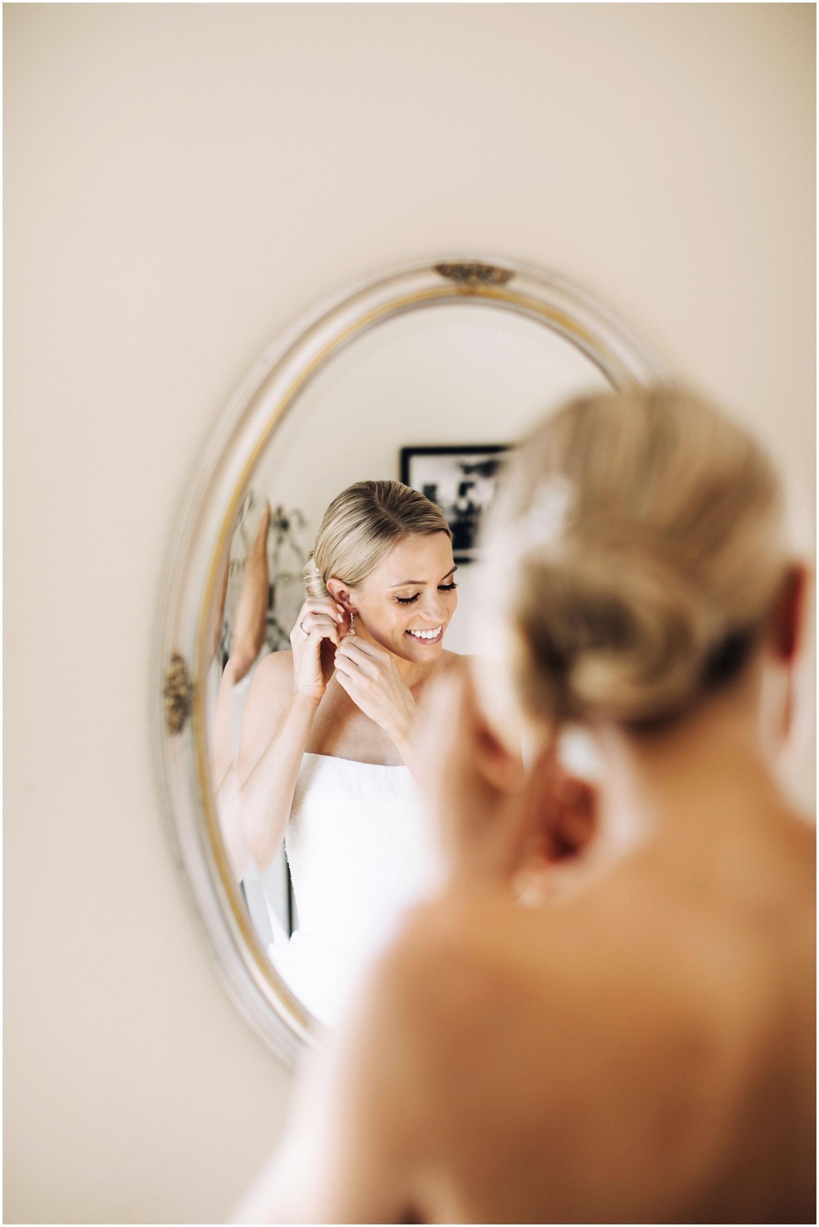 Minnesota Wedding Planner. Lafayette Club Wedding. Bride putting on her earrings