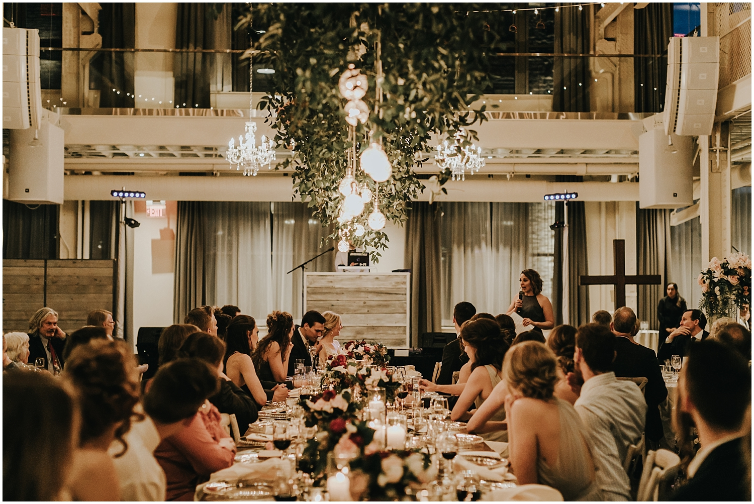 overhead greenery and lights in wedding reception