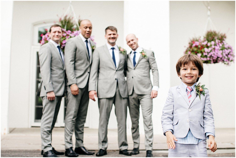groom and groomsmen looking at the ring bearer