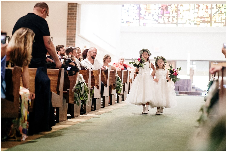 flower girls walking down the aisle at church wedding