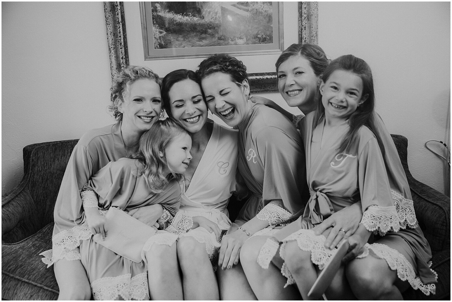bride laughing with her bridesmaids and flower girl